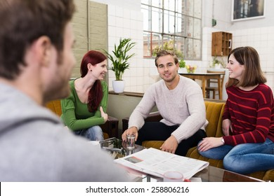 Group of Young White Friends Relaxing at the Living Room Area While Sharing Happy Moments.