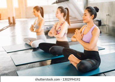 Group of young woman doing yoga on gym - beautiful lights.relax in nature on gym .Young sporty woman stretching.