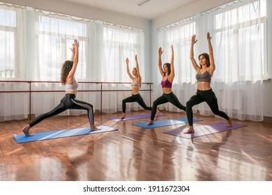 Group of young womans fitness instructor in Sportswear Leggings and Tops, stretching in the gym before pilates, on a yoga mat near the large window on a sunny day, female fitness yoga routine concept.