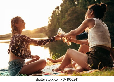 Group of young women celebrating at a lake. Young friends are toasting each other with beers during sunset at the lake.