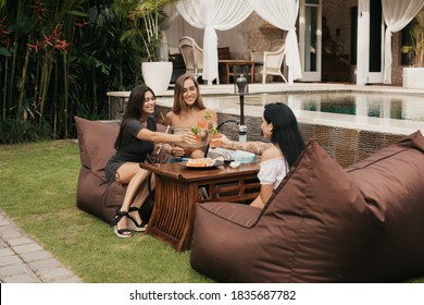 Group of young women with dark hair drinking and smoking a hookah or shisha, exhaling white smoke on a bean bags. Evening rest in an outdoor sushi bar. Summer. Vacation.