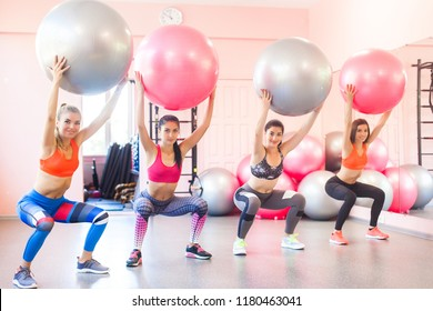 Group of young women doing exercises with fitballs. Pair exercises for fitness