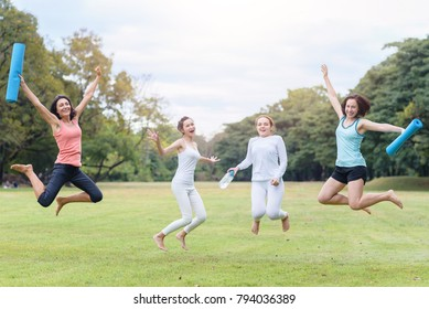 Group of young women doing yoga exercise outdoors in park. Happy friends jumping
