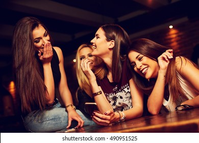 group of young women friends having fun looking at something funny on their smart phone and laughing