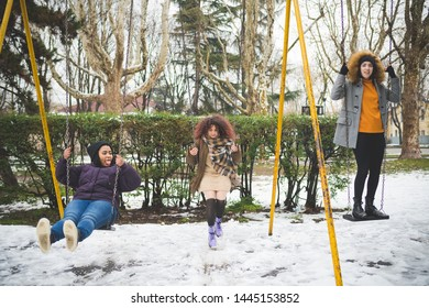 group of young women having fun on the swing outdoor in winter day – movement, enjoyment, youth