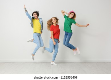 Group of young women in jeans and colorful t-shirts jumping near light wall