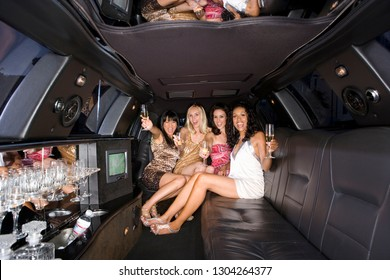 Group of young women on night out with drinks in limousine