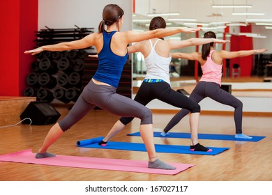 Group of young women practicing the warrior yoga pose during a class in a gym