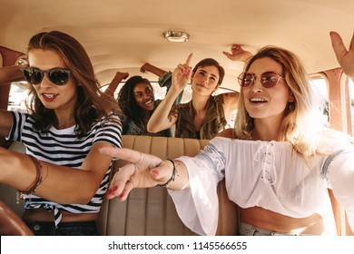 Group of young women singing and dancing in the car on a road trip. Multiracial female friends having fun on a car ride.