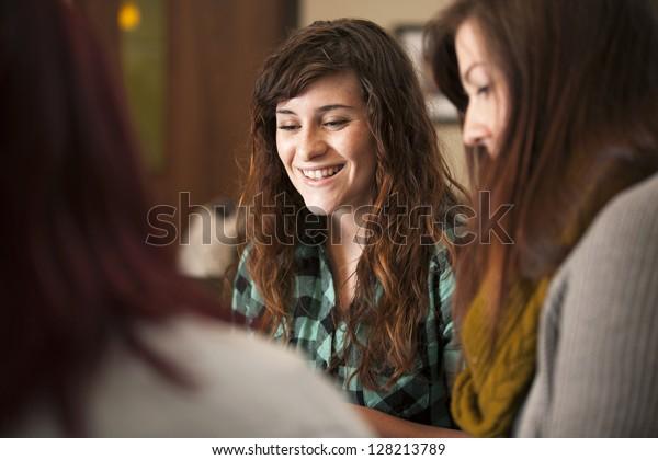 Eine Gruppe junger Frauen sitzt zusammen und lächelt.