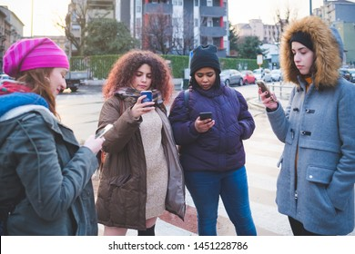 group of young women standing in the street and interacting with smartphone– togetherness, technology, friendship