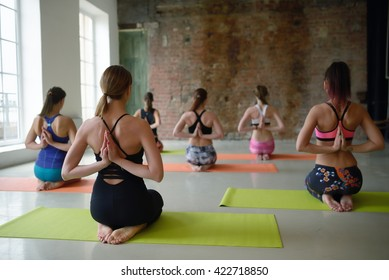Group young women stretching and practices yoga