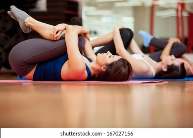 Group of young women stretching and warming up for a gym class