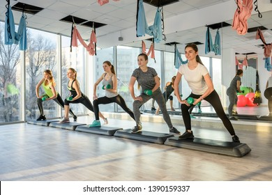 Group of young women training in gym with barbells