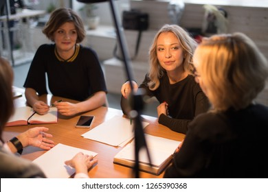 Group of younghardworking european young women working late at night in meeting room trying to complete their assignments.
