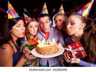 group of youths blows out the candles on a cake at a birthday party