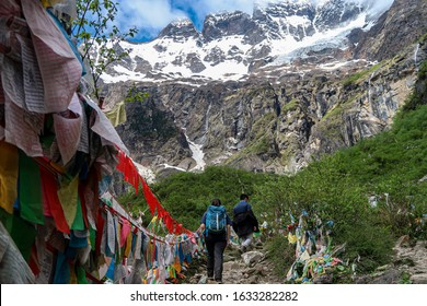 A group of youths hiking towards the Sacred Waterfall as part of the Yubeng village trek, located at mountainous regions in Yunnan, China. Meili snow mountains and Tibetan prayer flags can be seen.