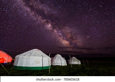Group of yurts against the starry sky at night in the desert.