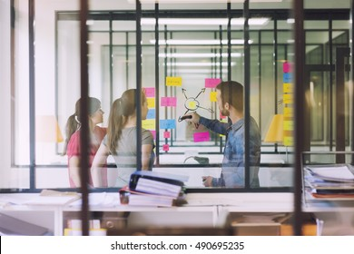 Groupe of casual business people working in front of glass wall using notes papers post it. Seen through glass in Startup office.