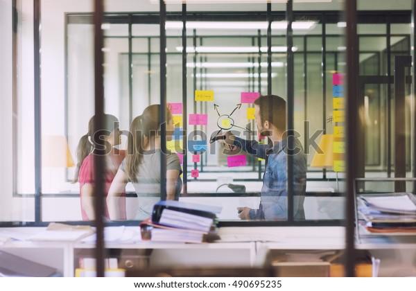 Группа случайных деловых людей, работающих перед стеклянной стеной, используя заметки бумаги разместить его. Видел через стекло в Стартап офисе.