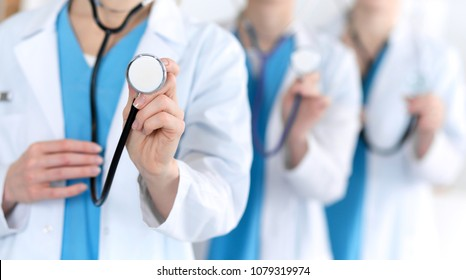Groupe of medicine doctors hold stethoscope head closeup. Physicians ready to examine and help patient. Medical help and insurance in health care, best treatment concept. Photo for advertisement