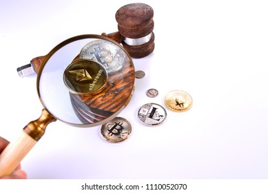 A grouping including a judges gavel sound block magnifying glass silver dimes and crypto currency including bit lite and ethereum coins.