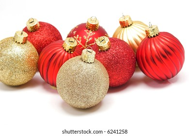 A grouping of red and gold Christmas ornaments.  Focus on front ornament.