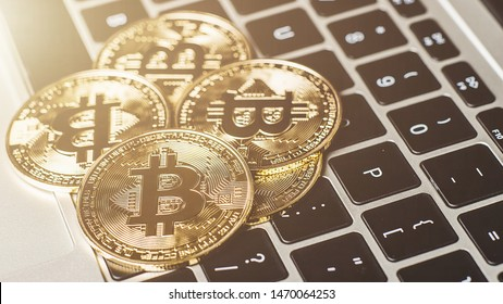 Groups of bitcoin is perched on the keyboard of the laptop. Crypto currency concept.