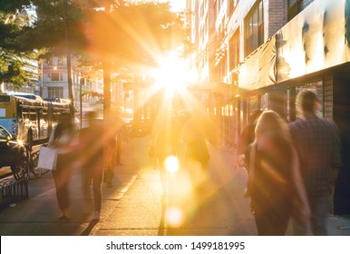 Groups of busy people walking down the crowded sidewalks of 14th Street in New York City with the summer sunset shining bright in the background