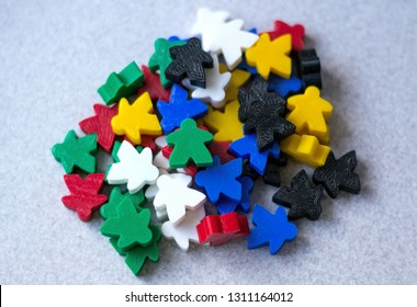 Groups of colorful meeples components of game on gray background. Small figures of man. Board games concept. Happiness and fun time passing. Carcassone game play.