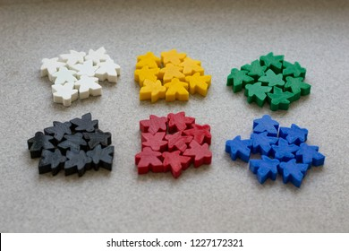 Groups of colorful meeples isolated on gray background. Blue, red, black, green and yellow. Small figures of man. Board games concept. . Business strategy. Components of card games.