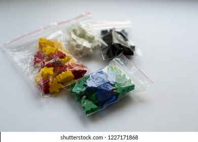 Groups of colorful meeples in pack isolated on gray background. Blue, red, black, green and yellow. Small figures of man. Board games concept. Couple of leaders of community. Business strategy.