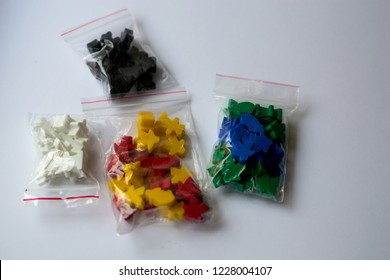 Groups of colorful meeples in pack isolated on gray background. Blue, red, black, green and yellow. Small figures of man. Board games concept. Couple of leaders of community. Business strategy