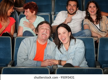 Groups of friends in the audience laugh and smile