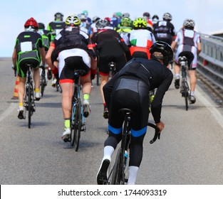 groups of many professional cyclists in the race in the city with the road climbed