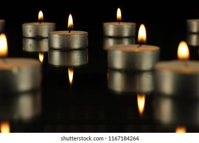 Groups of metallic gray canldes lit with flame and candle reflected on glass tabletop on black background.