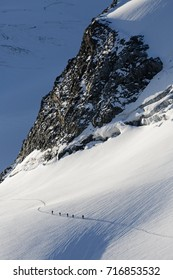 Groups of mountaineers crossing a glacier with crevasses on the sunrise