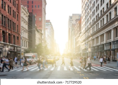 Groups of people walking across a busy crosswalk intersection in New York City with the glow of the sun in the background