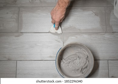 Grouting tiles seams with a rubber trowel. worker applies grout whit rubber trowel tiles