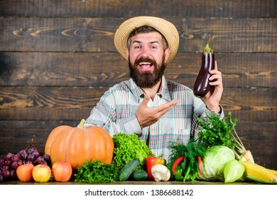 Grow organic crops. Homegrown organic food. Man with beard wooden background. Farmer with organic vegetables. Gardening and farming systems prescribe specific techniques. Organic horticulture concept.