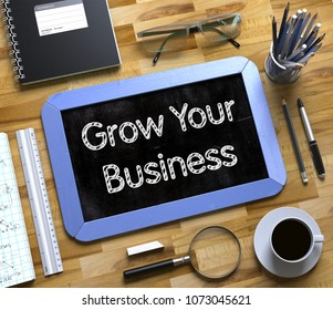 Grow Your Business - Text on Small Chalkboard.Blue Small Chalkboard with Handwritten Business Concept - Grow Your Business - on Office Desk and Other Office Supplies Around. Top View. 3d Rendering.