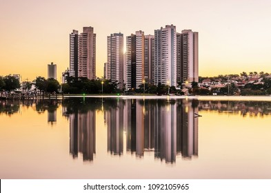 Growing city with few tall buildings reflected on the water of a lake, sunset hour - golden hour. Campo Grande MS, Brasil.