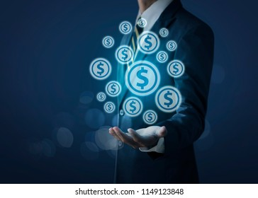 Growing money concept for business investment and finance. Businessman holding money coin icons (USD or US dollar) on dark tone background