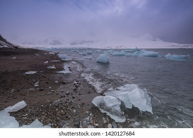 growlers of ice at beaach of Svalbard in the arctic ocean with dramatic sky above