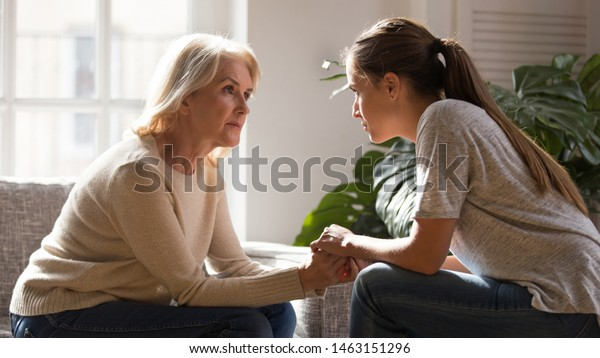 Grown up daughter holding hands of middle aged mother relatives female sitting look at each other having heart-to-heart talk, understanding support care and love of diverse generations women concept