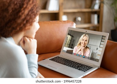 Grown daughter talk via video call on the laptop with a senior mother, lying on the couch and looks at the webcam. Two women differente generation have video meeting on the distance
