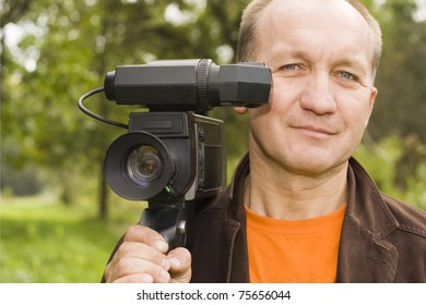 a grown man posing with a video camera on his shoulder.