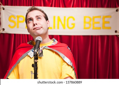 A grown man pretending to be a young boy competing in a spelling bee.