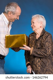 A grown son and aging mom with present box on a blue background