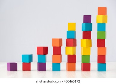 growning stack of colorful wood cube building blocks on white wood floor